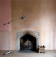 This gothic stone fireplace has been set into the bare plaster wall of this living room