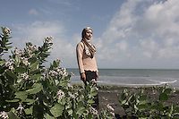 """Indonesia – Sumatra – Band Aceh – Salmi Hardiyanti, a 23-year-old tsunami survivor stands on the beach close to where she grew up. Salmi lost 23 relatives, including her grandparents, two younger sisters and her mother, who was pregnant at that time. Salmi says she will never forget how she felt after seeing the village completely destroyed, the foundations were the only thing left of what was her family house. """"People were telling me they couldn't find my mother. I had never cried so hard and so desperately in my life"""". Today, Salmi works as a tourist guide in Banda Aceh, precisely on one of the several tsunami stranded boats which have become a landmark tourist attractions within the city."""