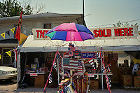 "An impromptu tent sits along the roadside in Kentucky advertising fireworks and Independence Day decorations for sale. A ""no smoking"" sign is posted on one of the tables."