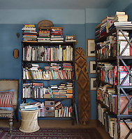 An antique shield from Papua New Guinea stands proped up in the study, surrounded by bookcases. The chair is by Robshaw