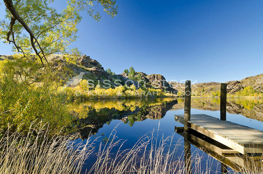 A clear Autumn day gives a perfect reflection in the water at Lower Manorburn Dam near Alexandra, Central Otago, South Island, New Zealand. Stock photos, Canvas prints, fine art prints