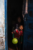 Young children peep out of the door during a house to house polio drive in Basantpur Sainthly village in Ghaziabad, Uttar Pradesh, India.