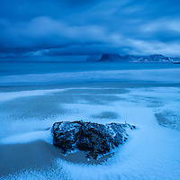 Waves wash over snow covered sand in winter at Storsandnes beach, Flakstadøy, Lofoten Islands, Norway