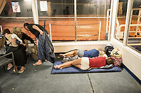 During their ferry ride to Athens, a Syrian family arranges their few belongings while two bare legged female tourists rest on their camping mattresses at their feet. Kos, Greece. Sept. 7, 2015