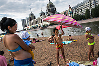 Women and children relax on a man-made beach on the banks of the Ishim River.