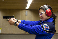 Switzerland. Geneva. A female police officer is aiming her Glock hand gun at firing range. The policewoman is training at the Police education center (Centre de formation de la Police. CCFP). She is using a Glock pistol which is a semi-automatic pistol designed and produced by Glock Ges.m.b.H. Glock was the first manufacturer to introduce ferritic nitrocarburizing into the firearms industry as an anti-corrosion surface treatment for metal gun parts. 22.03.12 &copy; 2012 Didier Ruef