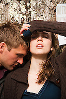 Young couple leaning on tree, her looking at camera with arm blocking the sun