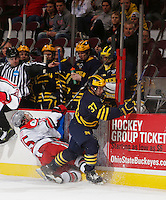 Mac Bennnett of Michigan slips by OSU #15 Nick Oddo in the first period at Value City Arena in Columbus Dec. 2, 2013.