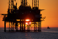 Stock photo of the silhouette of an offshore drilling rig at sunset off of Galliano, Louisiana