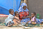 A family displaced displaced by war in the neighboring  Darfur region of Sudan eat a meal in the Goz Amer refugee camp in eastern Chad. A quarter million Darfur refugees live in camps in Chad. Another 2.3 million are internally displaced within Sudan.