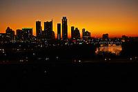 A vivid sunrise overshadows the Austin texas city skyline silhouette and Colorado River