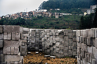 Concrete blocks lay in piles ready to be used in road construction outside of Pangzhihua Village, Yuanyang County, Yunnan Province, China.  Roads in the area are being developed to improve tourism and business in the rural, mountainous region.