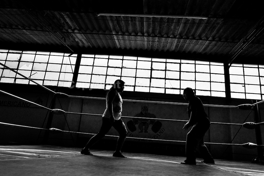 """A female Lucha libre wrestler trains with her coach at a combat sports gym in Mexico City, Mexico, 29 April 2011. Lucha libre, literally """"free fight"""" in Spanish, is a unique Mexican sporting event and cultural phenomenon. Based on aerial acrobatics, rapid holds and the use of mysterious masks, Lucha libre features the wrestlers as fictional characters (Good vs. Evil). Women wrestlers, known as luchadoras, often wear bright shiny leotards, black pantyhose or other provocative costumes. Given the popularity of Lucha libre in Mexico, many wrestlers have reached the cult status, showing up in movies or TV shows. However, almost all female fighters are amateur part-time wrestlers or housewives. Passing through the dirty remote areas in the peripheries, listening to the obscene screams from the mainly male audience, these no-name luchadoras fight straight on the street and charge about 10 US dollars for a show. Still, most of the young luchadoras train hard and wrestle virtually anywhere dreaming to escape from the poverty and to become a star worshipped by the modern Mexican society."""