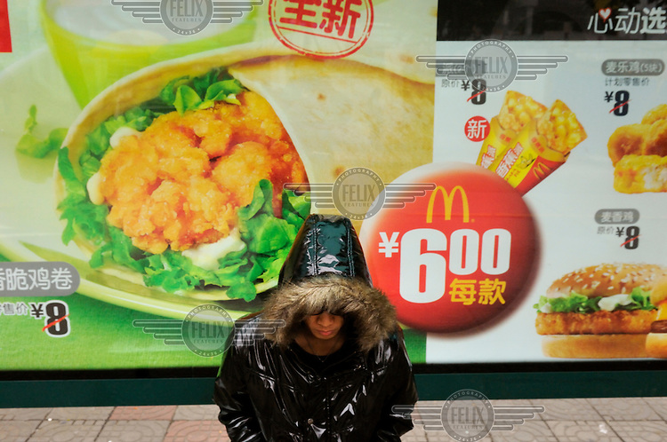 Youth with his hood up sitting waiting for a bus in front of a McDonald's advert.