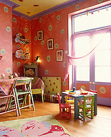 This children's nursery is an exuberance of colour with strawberries painted on the ceiling and radiator, the walls an hypnotic red, and each chair painted a different colour