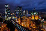 The elevated Medellin Metro is a colorful blur as it glides into the Parque Berrio Metro Station in front of the illuminated Palace of Culture in Plaza Botero.