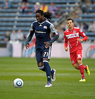 New England midfielder Shalrie Joseph (21) dribbles the ball as Chicago midfielder Marco Pappa (16) looks on.  The Chicago Fire defeated the New England Revolution 3-2 at Toyota Park in Bridgeview, IL on Sept. 25, 2011.
