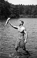 sexy man in a lake holding a fish