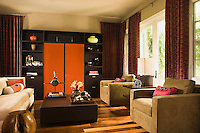 Bright orange panels in the bespoke storage unit of the living room make a bold statement and cleverly conceal the entertainment system