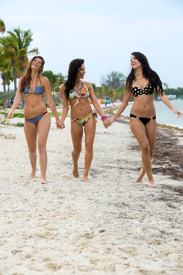 Three laughing sexy young women in bikinis walking hand in hand along the beach