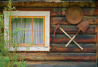Pick axe and gold pan hanging on the outside wall of an old mining and trapping cabin, Livengood, Alaska