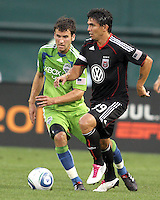 Jaime Moreno #99 of D.C. United moves past Nathan Sturgis #12 of Seattle Sounders FC during an MLS match at RFK Stadium on July 15 2010, in Washington DC.Seattle won 1-0.