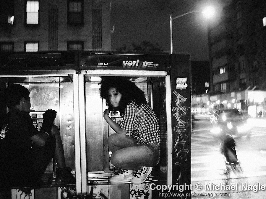 NEW YORK -- JUNE 20, 2008:  Teenagers plaing hide and seek at night, hide from friends in a Verizon phone booth in the East Village on June 20, 2008 in New York City.  (PHOTOGRAPH BY MICHAEL NAGLE)