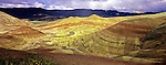 Panorama of sunlit Painted Hills with foreground flowers, distant rainbow and rain clouds. John Day Fossil Beds National Monument, Mitchell, Oregon. Taken with XPan 30mm lens.