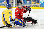 Greg Westlake offers some words of inspiration to one of the Swedish players during 2010 Paralympic Games sledge hockey action at UBC Thunderbird Arena in Vancouver. Credit: CPC/HC/Matthew Manor.