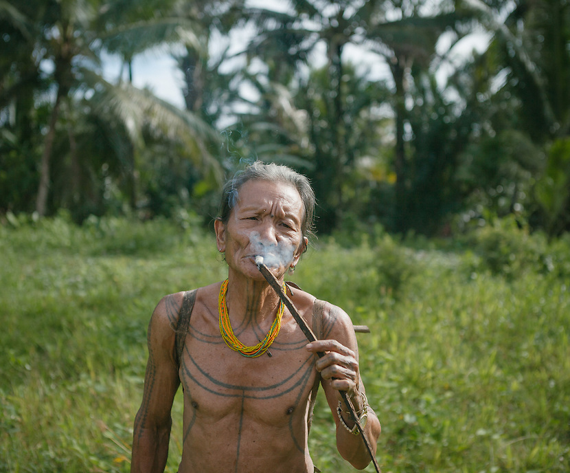 A Mentawai shaman, or locally called Sikerei, is lighting his cigars made from banana leaf. The Mentawai are the tribes living traditionally in the island of Siberut, Indonesia. Here, where the changes came slow, some of the people are still living like their ancestors did centuries ago. They s till practice ancient religion called Arat Sabulungan, which believe that everything in the forest has a spirit.