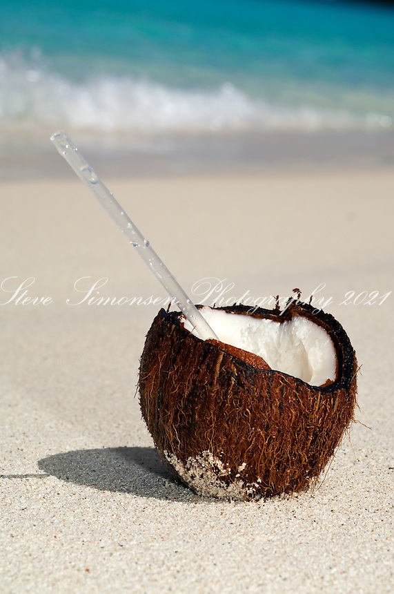 Coconut with a straw on the sand.Honeymoon Beach, St John.Virgin Islands National Park