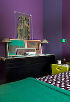 The deep purple tones of the bedroom walls and the black painted chest of drawers provide a stunning backdrop for some framed swatches of vintage fabric