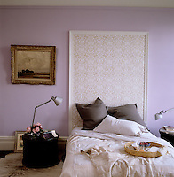 A simple board has been covered in patterned wallpaper and used as a headboard