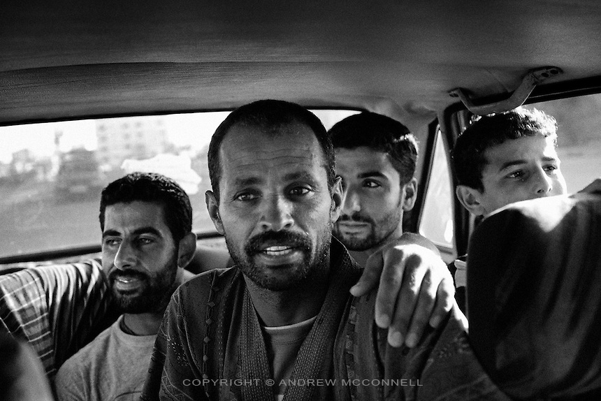 Surfers L-R, Ahmed Abu Hassira, 32, Mohammed Abu Jayab, 38, Kahlil Alhassani, 24, and Mahmoud Bakeat, 13, ride in a taxi to the beach in Gaza City, Gaza Strip. Mohammed Abu Jayab is one of Gaza's first surfers and leads a group of 11 surfers.