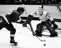 Seals goalie Gilles Meloche stops shot by Red Wing Marcel Dionne. (1975 photo/Ron Riesterer)