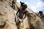 LUBUMBASHI, DEMOCRATIC REPUBLIC OF CONGO - DECEMBER 13: A young boy works among 4,000 artisan miners who dig copper on December 13, 2005 in Ruashi mine about 20 kilometers outside Lubumbashi, Congo, DRC. Some children as young as eight work in the mine under dangerous conditions. Every month a few of the miners are killed. Congo has one of the largest Copper deposits in the world and most of it is exported to China. It?s fueling the thirst for minerals for China?s economic boom. The young men who works in the mine makes a few US dollars a day, and the children much less. The mine is about one hundred years old and has been a source of wealth for the Katanga province for many years. In recent years many foreign companies and shady business people has moved into Congo to plunder its wealth. The country has no elected government and the corruption is rife. Border and customs officials are easily bribed. Congo has had a civil war since 1997 and it?s estimated that nearly 4 million people has died in fighting and because of lack of health care. (Photo: Per-Anders Pettersson/Getty Images)