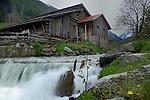 Old wooden farm building alongside fast flowing mountain stream. Gries. Sölden district, Tyrol, Tirol, Alps Austria.