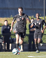Brown University midfielder Michel Comitis (14) brings the ball forward. Brown University (black) defeated Boston College (white), 1-0, at Newton Campus Field, October 16, 2012.
