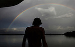 Scot Janikula takes a look from the back of his boat at a rainbow that appeared after a summer storm rolled through the community of people living on their boats anchored in Estero Bay.