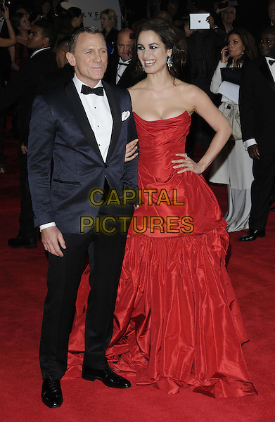Daniel Craig, Berenice Marlohe.'Skyfall' Royal World Film Premiere, Royal Albert Hall, Kensington Gore, London, England..23rd October 2012.full length black strapless dress cleavage gathered hand on hip red tuxedo white shirt bow tie smiling .CAP/CAN.©Can Nguyen/Capital Pictures.