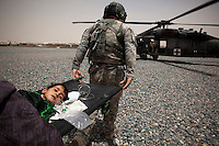 US Army medics from Charlie Company, Sixth Battalion, 101st Aviation Regiment transfer a young girl with a serious head injury onto a medevac helicopter near Kandahar.