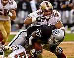 San Francisco 49ers linebacker Jeff Ulbrich (53) tackles Oakland Raiders running back Tyrone Wheatley (47) on Saturday, August 24, 2002, in Oakland, California. The Raiders defeated the 49ers 17-10 in a preseason game.