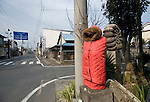 A Buddhist statue is dressed in a thick coat to protect it against the elements in Minami-Soma, Fukushima Prefecture, Japan on 30 March, 2011.  Photographer: Robert Gilhooly
