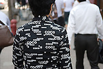 Woman wearing a jacket with Coco signs on it in reference to Chanel, Shanghai, China.