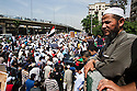 An Egyptian salafi man watches a mix of revolutionary youth and Islamist groups march through the Abbasiya district during May 4, 2012 demonstrations against the ruling Supreme Council of the Armed Forces (SCAF) near the Defense ministry building in Cairo, Egypt. Although the salafis and youth revolutionaries draw from different ends of the political spectrum, they have managed to find common ground in demonstrations against the Supreme Council of Armed Forces (SCAF) and in their support of Egyptian Islamist presidential candidate Abdul Moneim Aboul Fotouh.