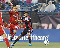 Toronto FC forward Jeremy Brockie (22) intercepts and breaks for the goal as New England Revolution defender Stephen McCarthy (15) defends. In a Major League Soccer (MLS) match, the New England Revolution (blue) defeated Toronto FC (red), 2-0, at Gillette Stadium on May 25, 2013.