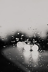 black and white photograph of car headlights, blurred through a rain covered window