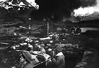 Japanese attack on Dutch Harbor, June 3, 1942.  Group of Marines on the &quot;alert&quot; between attacks.  Smoke from burning fuel tanks in background had been set afire by a dive bomber the previous day.  Alaska. (Navy)<br /> NARA FILE #:  080-G-12076<br /> WAR &amp; CONFLICT BOOK #:  1147