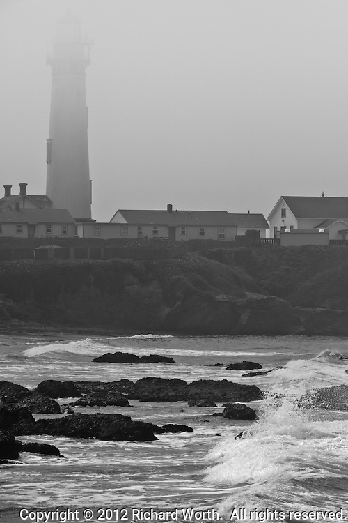 Fog hovers over the top of the Pigeon Point Lighthouse while waves flow over the rocks below.