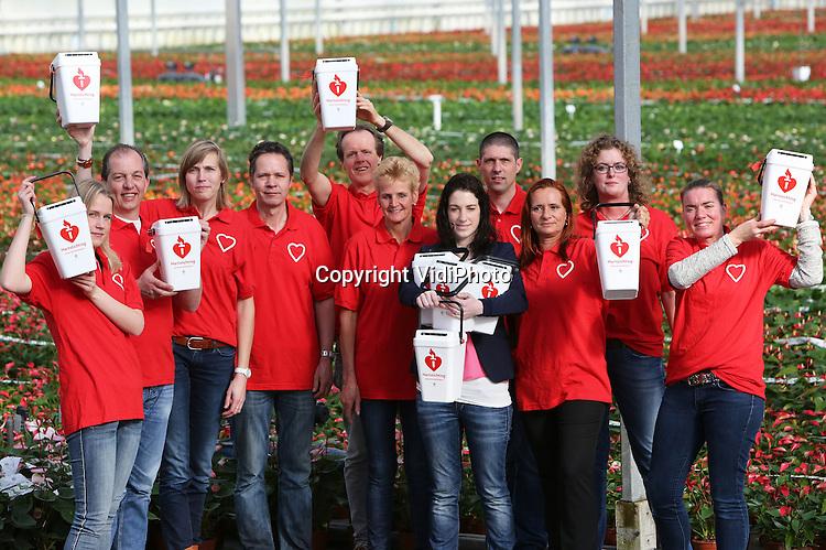 Foto: VidiPhoto<br /> <br /> NAALDWIJK - Nederlandse anthuriumkwekers kwamen donderdag massaal naar Naaldwijk om zich in te laten schrijven als collectant voor de Nederlandse Hartstichting. De stichting zoekt 2000 vrijwilligers voor de landelijke collecteweek van 5-11 april en is op dit moment bezig met een succesvolle wervingscampagne. Anthuriumkwekers willen zich inzetten voor de Hartstichting. De bloemen van de anthurium hebben namelijk de vorm van een hart. De kwekers gaan niet alleen met een collectebus langs de deuren, maar een deel van de verkoop van hun planten via tuincentra en bloemisten komt ten goede aan de Hartstichting. Inmiddels hebben ruim duizend mensen zich al ingeschreven als collectant. Foto: Hartpati&euml;nte Joyce de Roo (blauwe blazer) van de Hartstichting deelt de eerste collectebussen uit.